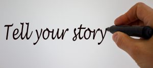 Hand writing Tell Your Story in expo marker