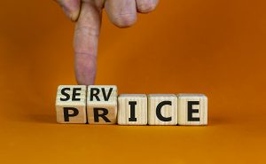 Service price symbol. Hand turns a cube and changes the words 'service' to 'price'. Beautiful orange background. Business and service price concept