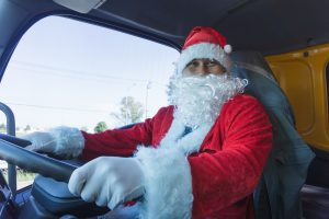 Santa Claus driving a truck. Truck driver wearing Santa Claus and smiling happy on Christmas Day. Workers in transportation and delivery business are working in celebration holidays. Merry Christmas