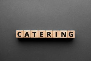 Catering - words from wooden blocks with letters, making or serving food catering concept, top view gray background