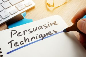 Man writing Persuasive Techniques in a note.