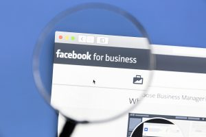 magnifying glass looking at Facebook for business page.