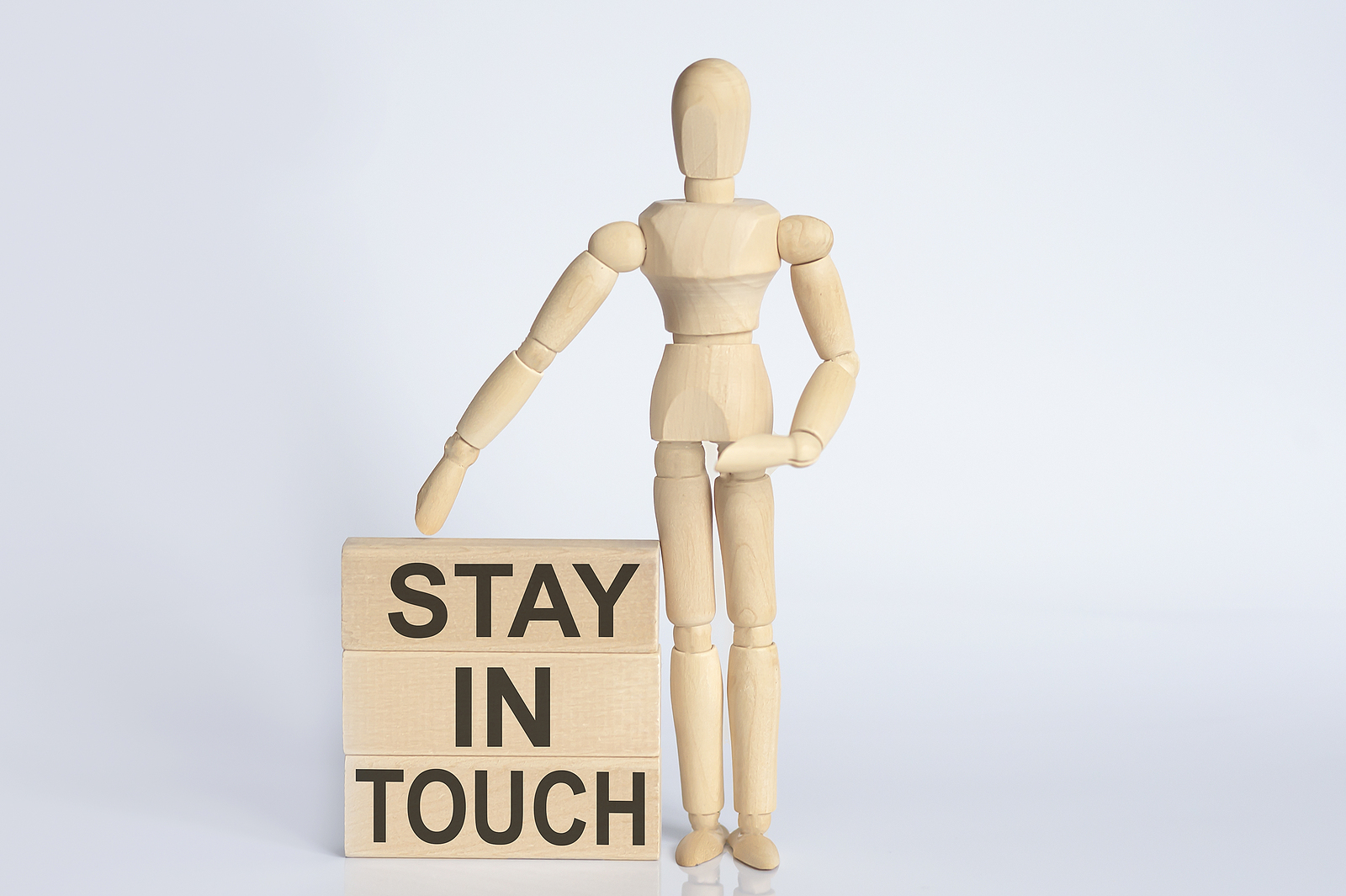 Wooden man shows with hand text Stay In Touch concept on wooden block