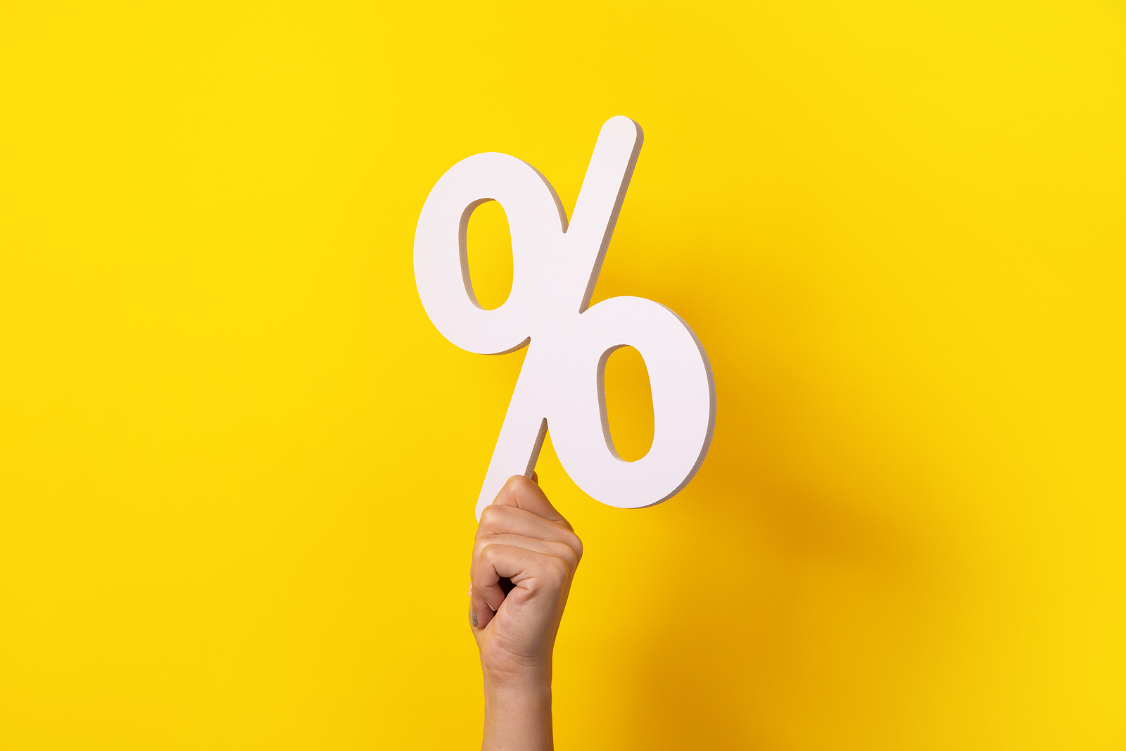 hand holding percentage sign over yellow background
