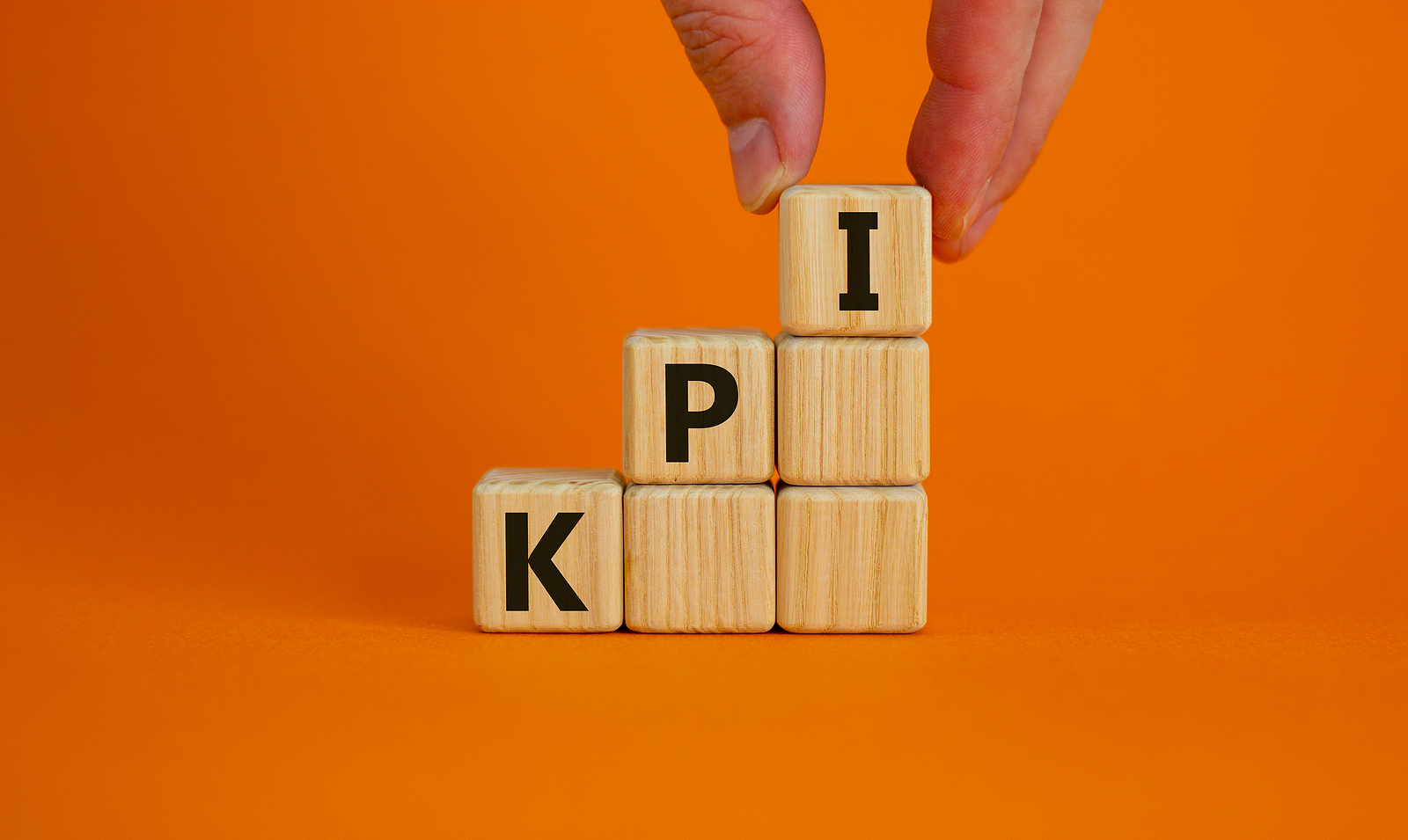 KPI symbol. Wood cubes with acronym 'KPI, key performance indicator' stacking as step stair on orange background, copy space. Male hand. Business and KPI concept.