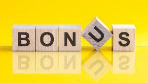 Bonus word written on wood block. Bonus word is made of wooden building blocks lying on the yellow table. Bonus, business concept, yellow background